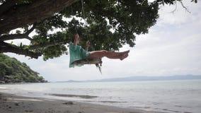 Молодая женщина отбрасывая на качаниях на пляже на тропическом острове сток-видео
