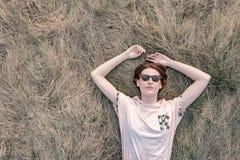 Молодая женщина отдыхает на траве наслаждаясь весной стоковые изображения rf