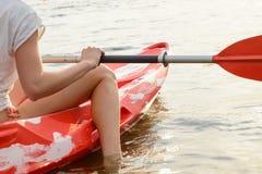 Молодая женщина отдыхая в каяке на красивых реке или озере на заходе солнца Закройте вверх по взгляду женских руки и ноги Стоковые Фото
