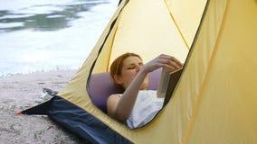 Молодая женщина отдыхая и книга чтения в шатре на природе Река на заднем плане Пеший туризм, перемещение, зеленый туризм акции видеоматериалы