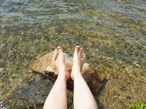 Молодая женщина отдыхая на озере стоковое фото rf