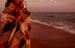 Молодая женщина отдыхая на пляже на заходе солнца стоковая фотография