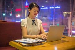 Молодая женщина офиса работая поздно стоковое изображение