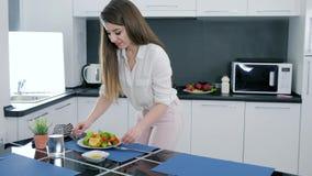 Молодая женщина очищает от кухонного стола после варить салат дома видеоматериал