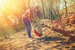 Молодая женщина очищает парк в субботу Консервация экологичности леса Подкраска стоковые изображения