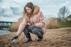 Молодая женщина очищает пляж от пластикового отхода стоковая фотография