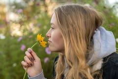 Молодая женщина пахнет на цветке стоковые фото