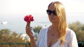 Молодая женщина пахнуть красными цветками в конусе waffle акции видеоматериалы