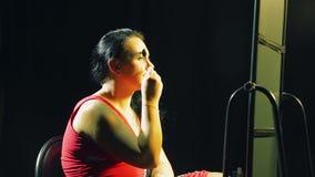 Молодая женщина перед зеркалом кладет дальше ее брови с щеткой сток-видео