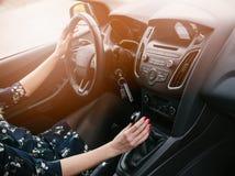 Молодая женщина переключать в автомобиле copyspace автомобиля управляя взглядом обеспеченным внутренностью стоковое фото rf