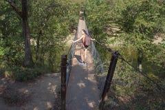 Молодая женщина пересекая реку на мосте веревочки Стоковое фото RF