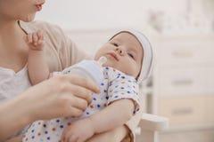 Молодая женщина подавая милый маленький младенец дома, Стоковые Фотографии RF