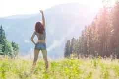 Молодая женщина поднимает ее руку на верхней части горы, свободном s Стоковая Фотография