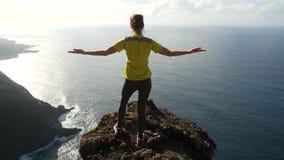 Молодая женщина поднимая ее оружия на красивой крутой скале над океаном, взгляд сверху Дама на саммите в красивом сток-видео