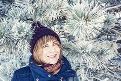 Молодая женщина под снежным хвойным деревом стоковое фото