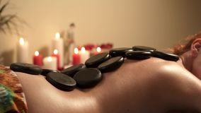 Молодая женщина получая горячий каменный массаж на салоне спа, конец вверх горячих камней на задней части сток-видео