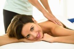 Молодая женщина получая задний массаж в спа-центре Стоковая Фотография RF