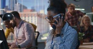 Молодая женщина получая звонок на офисе