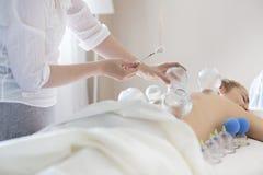 Молодая женщина получая обработку на медицинской клинике Стоковое Изображение RF