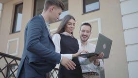 Молодая женщина портрета и 2 люд в официальной носке обсуждая проект на ноутбуке на террасе Отношение дела акции видеоматериалы