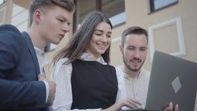 Молодая женщина портрета милая и 2 люд в официальной носке обсуждая проект на ноутбуке на террасе r акции видеоматериалы
