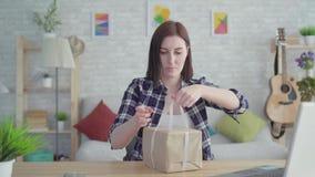 Молодая женщина портрета создает программу-оболочку подарок сидя на таблице акции видеоматериалы