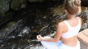 Молодая женщина практикует йогу и раздумье сидя в представлении лотоса на водопаде сток-видео