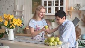 Молодая женщина предлагает ее парню зеленое яблоко, совместно они держит яблоко в их руках видеоматериал