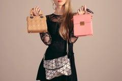 Молодая женщина представляя в черных платье и сумке 3 Стоковые Фото