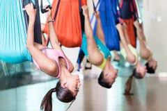 Молодая женщина пригонки практикуя воздушную йогу во время класса группы в спортзале стоковое изображение rf