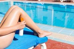 Молодая женщина прикладывает сливк солнца на ее ровных загоренных ногах бассейном Фактор предохранения от Солнца в каникулах, кон стоковая фотография rf