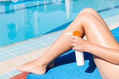 Молодая женщина прикладывает сливк солнца на ее ровных загоренных ногах бассейном Фактор предохранения от Солнца в каникулах, кон стоковое фото rf