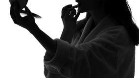 Молодая женщина прикладывая губную помаду перед зеркалом и усмехаясь, женственность, красота видеоматериал