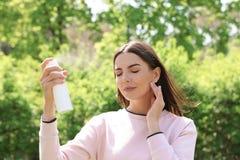 Молодая женщина прикладывая термальную воду на стороне Косметический продукт стоковое фото