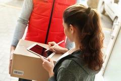 Молодая женщина прилагая подпись после получать пакет Стоковая Фотография
