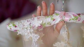 Молодая женщина принимает вешалку с белым платьем свадьбы видеоматериал