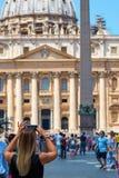 Молодая женщина принимает фото с мобильным телефоном в квадрате St Peterв Ватикане стоковые изображения rf