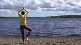 Молодая женщина приниманнсяый за фитнес на береге озера в течение дня сток-видео