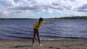 Молодая женщина приниманнсяый за фитнес на береге озера в течение дня акции видеоматериалы