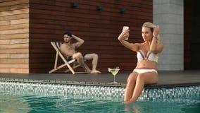 Молодая женщина принимая мобильное selfie в бассейне Сексуальная женщина представляя для selfie видеоматериал