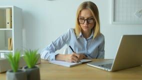 Молодая женщина принимая примечания пока работающ на компьтер-книжке сток-видео