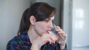 Молодая женщина принимая таблетку для того чтобы облегчить головную боль акции видеоматериалы