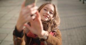 Молодая женщина принимая selfie с мобильным телефоном в солнечной улице города Стоковое Изображение RF