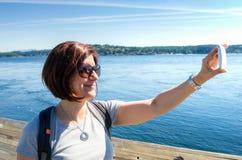 Молодая женщина принимая Selfie с океаном как предпосылка Стоковая Фотография RF
