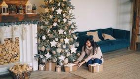Молодая женщина приносит подарочные коробки к рождественской елке и кладет их под ель после этого смотря настоящие моменты и сток-видео