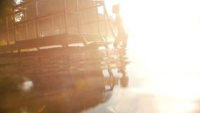 Молодая женщина приходя из воды красиво, изумляющ слепимость солнца акции видеоматериалы