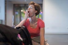 Молодая женщина при багаж ждать в зале авиапорта ее самолет Стоковые Фотографии RF