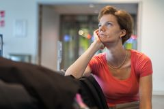 Молодая женщина при багаж ждать в зале авиапорта ее самолет Стоковое фото RF