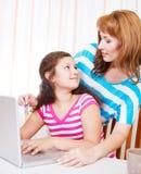 Молодая женщина при девушка используя портативный компьютер Стоковые Изображения RF