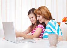 Молодая женщина при дочь используя портативный компьютер Стоковое Изображение